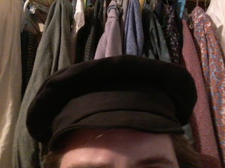 A newsboy or mechanic's style cap in black wool
