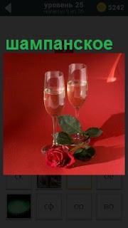 На красном фоне стоят два бокала с шампанским и рядом положена одна роза красного цвета