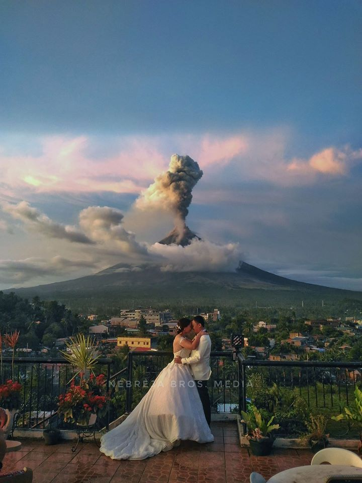 couple posed behind the raging Mayon Volcano