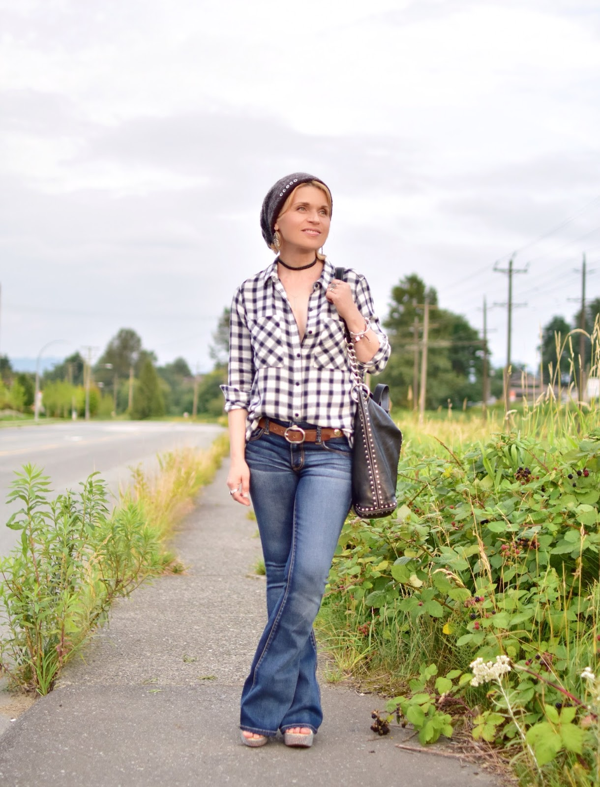 styling flare jeans with a plaid shirt, concho belt, mohair beanie, and MK bag