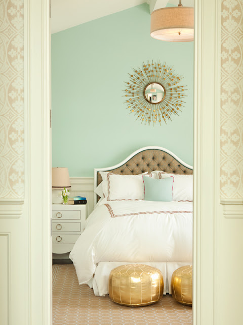 bedroom with mint walls and gold Moroccan poufs at the end of the bed, molded tufted headboard, and vintage nightstand