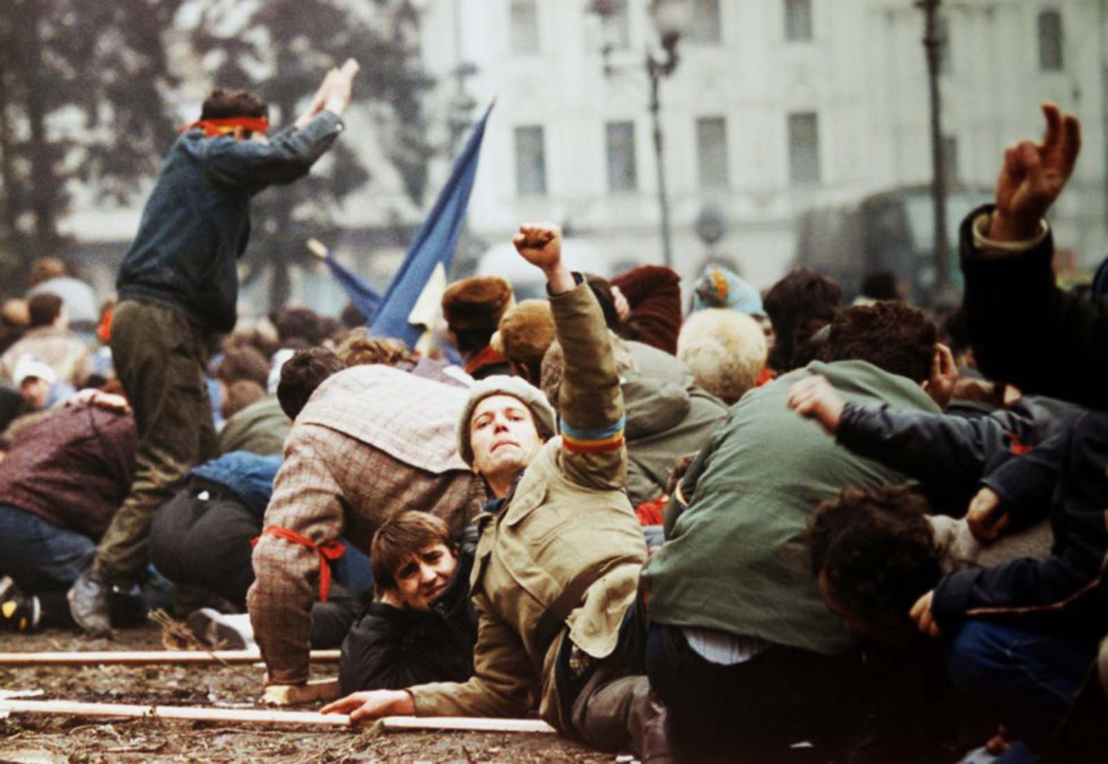 An anti-Ceaucescu revolutionary makes a V-sign as demonstrators lie on the ground to escape from the crossfire between the pro-Ceausescu troops and anti-regime supporters.