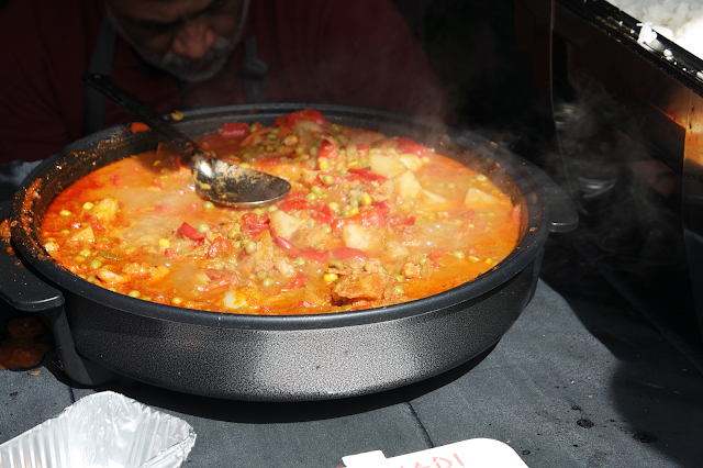 a curry simmering in a huge iron pot
