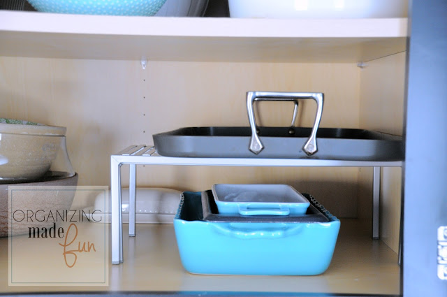 Use an expandable shelf to hold more serving dishes inside a cupboards :: OrganizingMadeFun.com