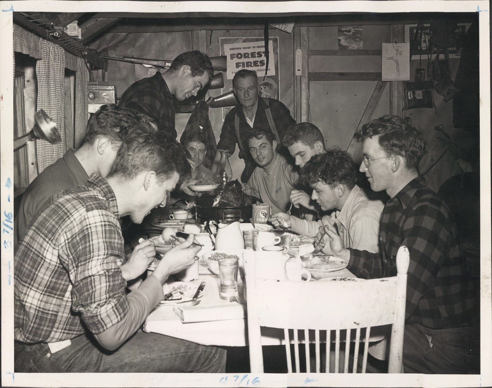 A black and white photograph of a group of men crowded around a dinner table for a meal.