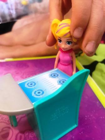C/U Hands of girl with Polly Pocket doll with stove