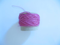 Side view of small cardboard reel of hot pink size 80 cotton thread.