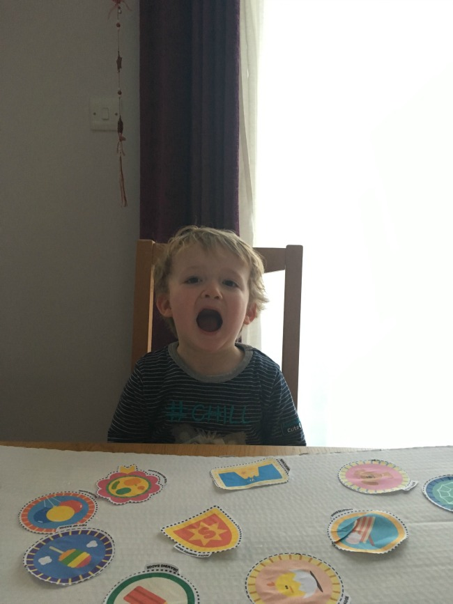 toddler-with-his-mouth-open-and-board-with-badges-stuck-on-it
