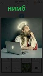 мужчина за столом у которого нимб на голове и рядом ноутбук