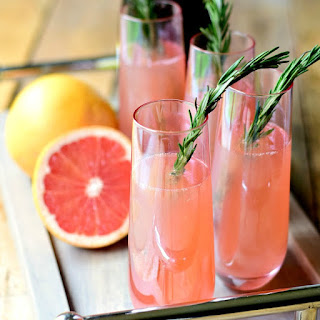 Rosemary Pink Grapefruit Mimosas on a wooden serving tray