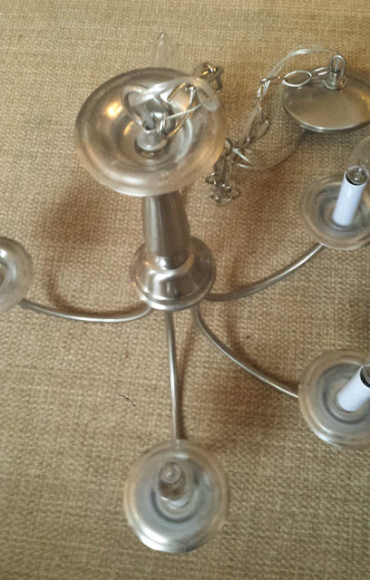 silver chandelier on floor, sisal carpet