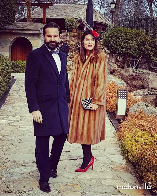Leticia de boda con abrigo de piel, medias negras tupidas, zapatos stilettos rojos  y tocado negro y rojo con plumas by malonsilla con pelo suelto