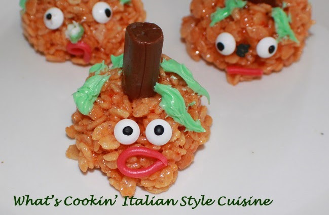 Halloween orange rice krispies pumpkin heads with tootsie rolls centers. These are a traditional recipe for rice krispie treats.