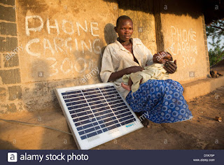 Mother with a solar panel in Lira District, Uganda, East Africa. (Credit: Alamy) Click to Enlarge.