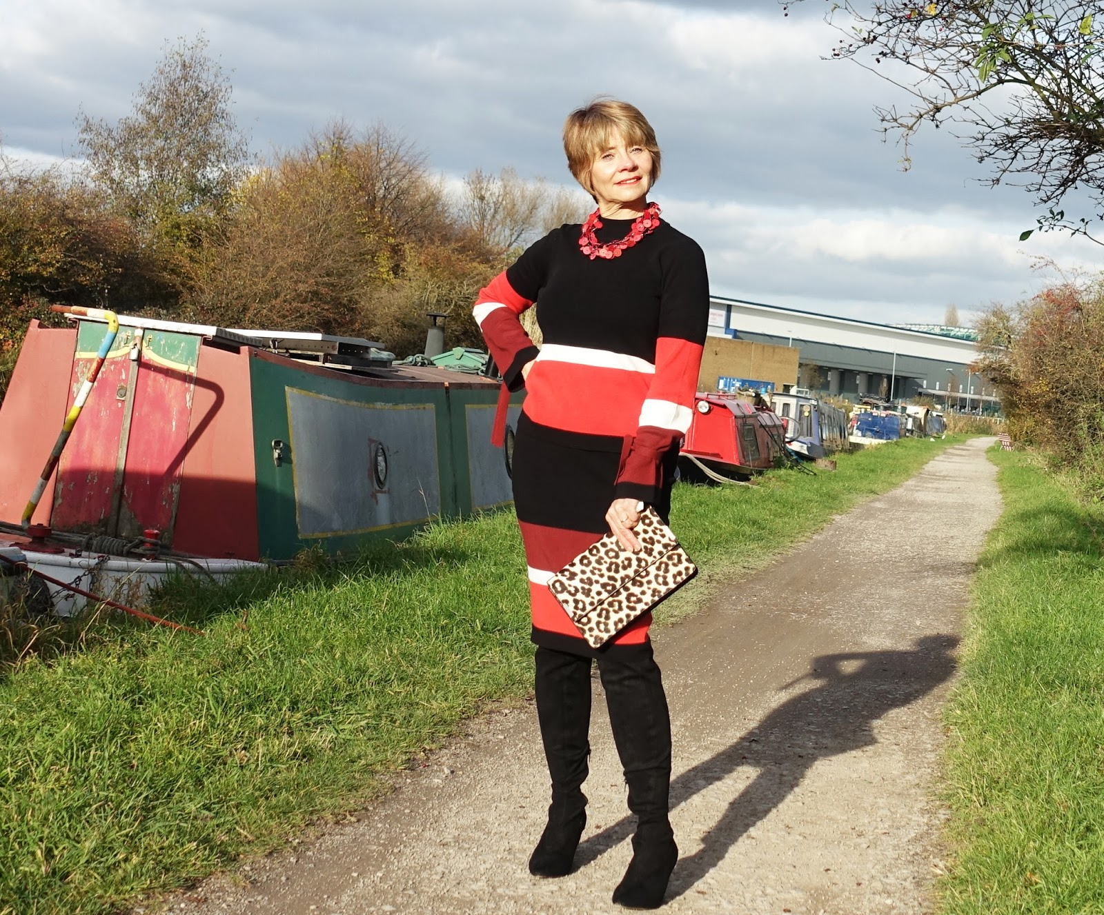 Image showing a 50 plus woman in a colour block jumper and skirt posing by barges