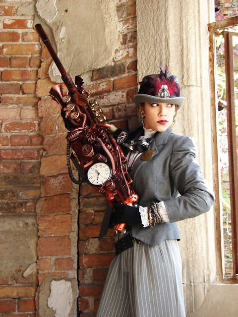 Woman cosplaying as female steampunk U.S. Marshal with large impressive steampunk gun. women's steampunk fashion, clothing, and cosplay