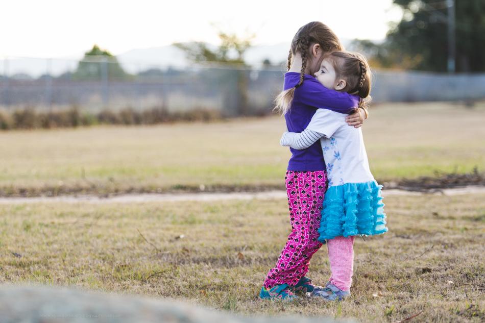 Sisters hugging outside