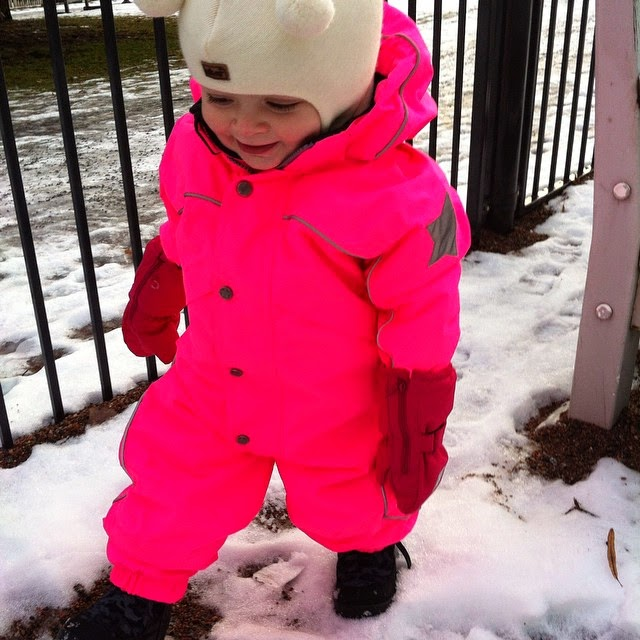 toddler wearing a neon pink snowsuit