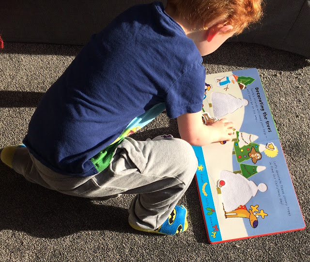 A 3 year old boy playing with an activity book