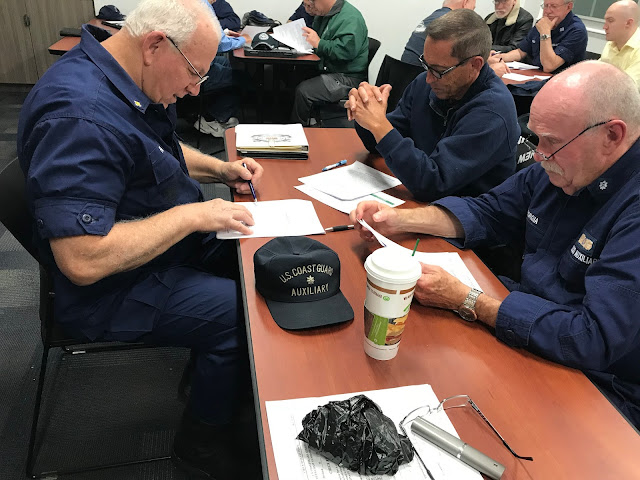 Three Auxiliary members are reading their team training exercise.