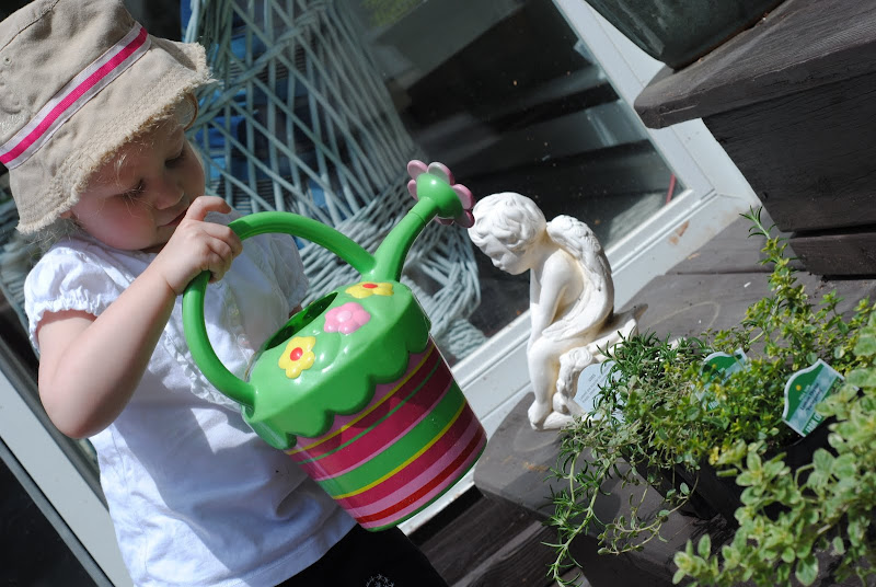 Little girl watering flowers with a watering can