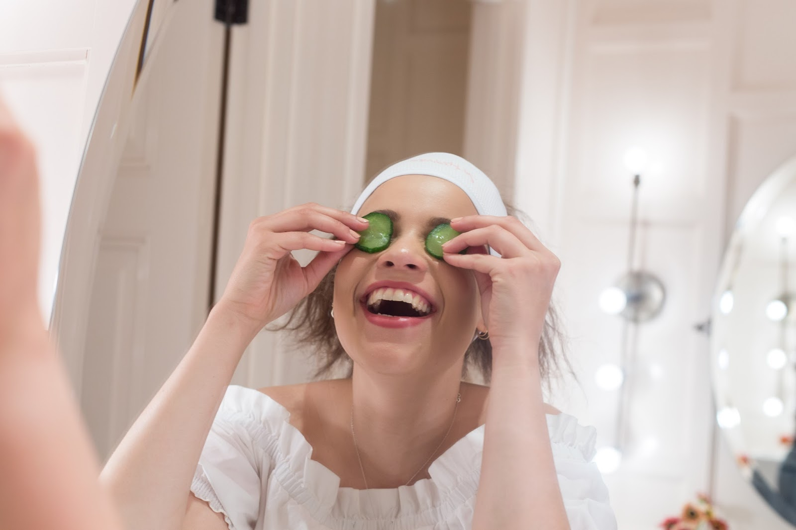 Image of Eboni laughing at the mirror whilst holding cucumber up to her eyes