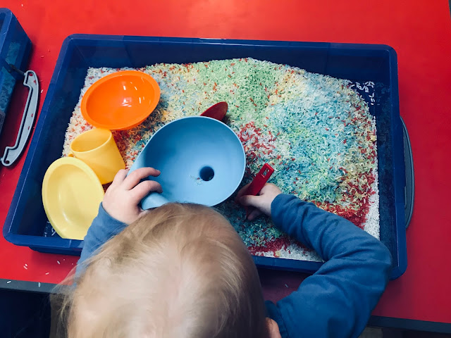 A toddler sitting in front of a tray of coloured rice with a spoon, bowl and funnels