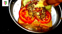 image of sprinkling grated cheese on bread
