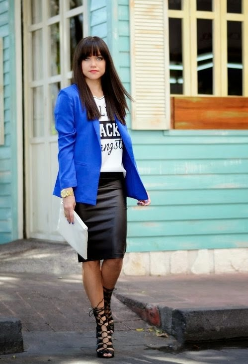 She is wearing a blue blazer, printed top, midi leather skirt