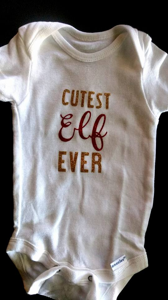 03380db4 This onesie, shown here, is a Christmas onesie by HappyCamperCrafters, over  on Etsy. It has the words, Cutest Elf Ever written across the onesie, ...