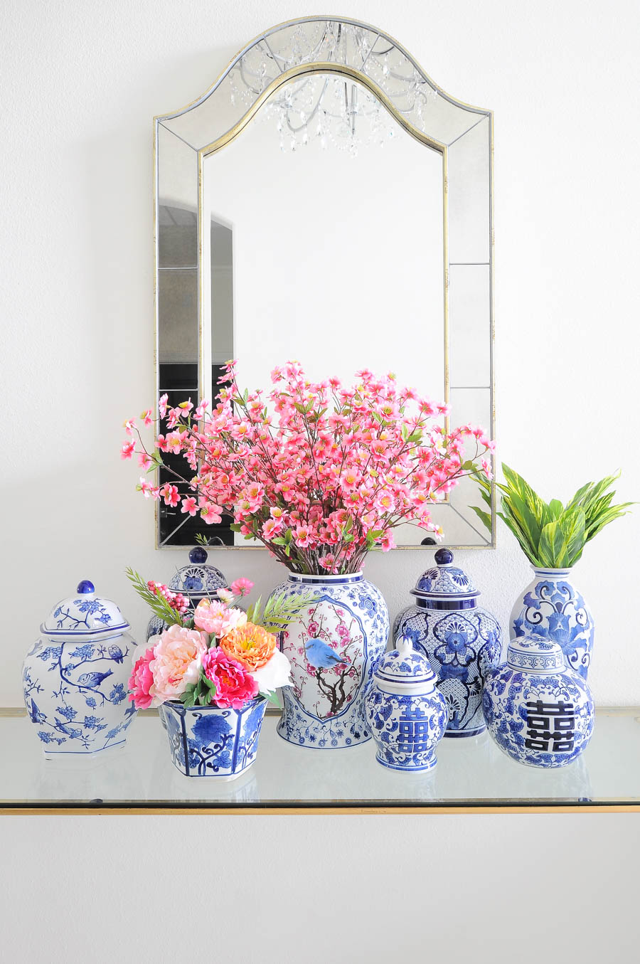 Ginger jars with florals look beautiful in front of a mirror in this stunning spring foyer home decor.