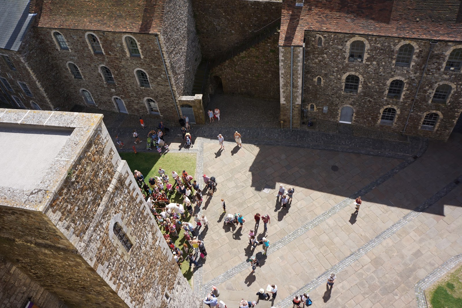 looking down from dover castle tower at lots of tiny people on the yard