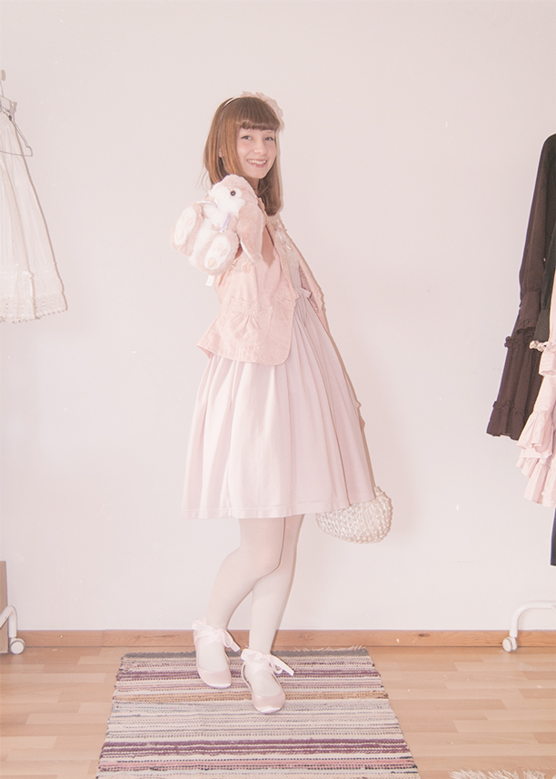 a girl dressed in a pink innocent world lolita dress holding a bunny plushie