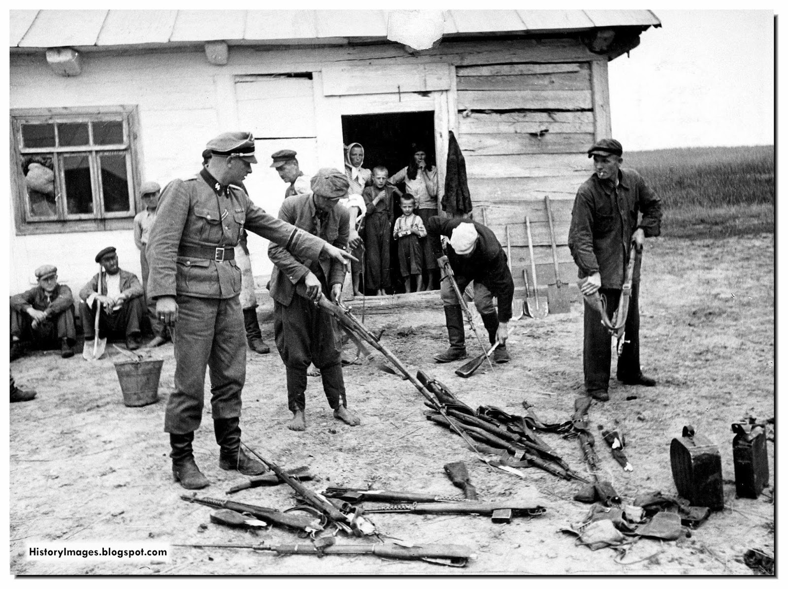 A German soldier orders Russian civilians gather captured Soviet arms.
