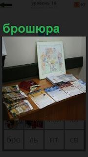 На столе представлены разные брошюры, в том числе газеты, журналы, книги