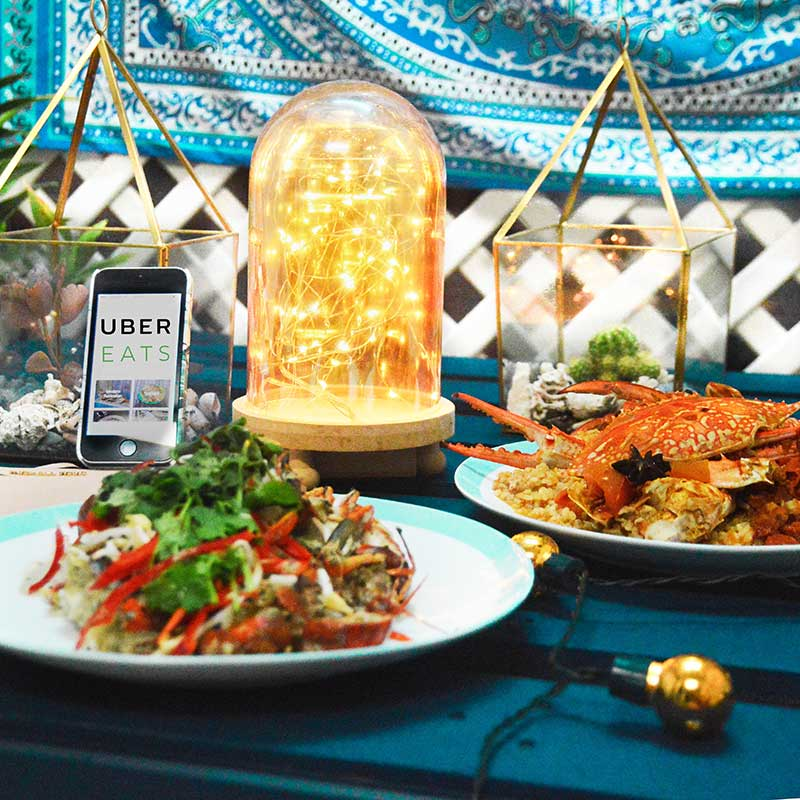 food flatlay with ubereats seafood from ochre and michael kors clutch