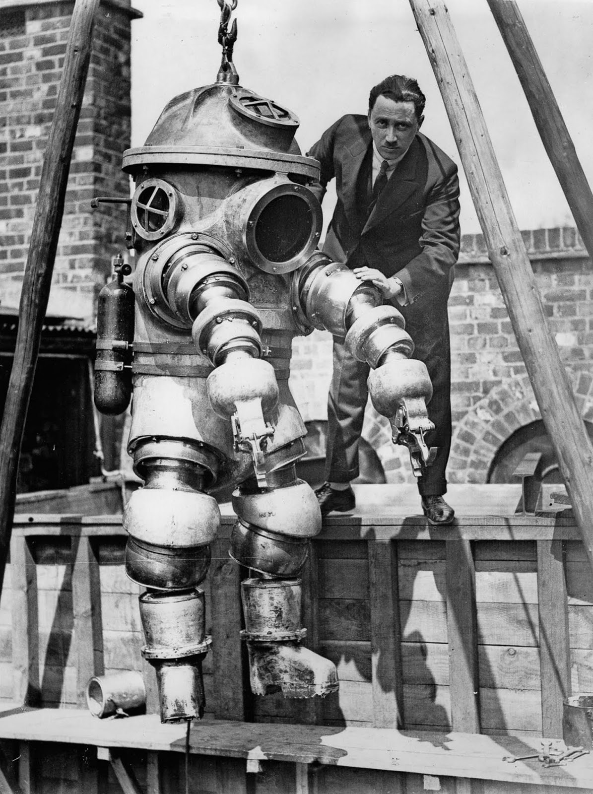 J.S. Peress, the inventor of a new armored diving suit, gets his device ready for tests in a tank at Weybridge, United Kingdom. 1930.