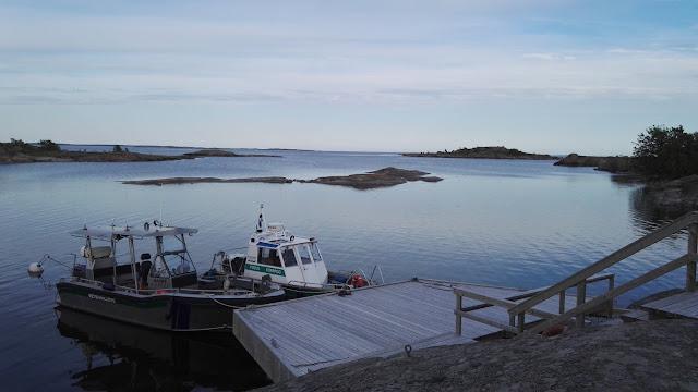Pieni laituri jossa kaksi venettä. Meri on tyyni.