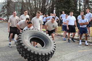 Army ROTC cadets cheer on their teammate during the tire flip tug-of-war competition.