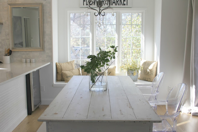 Modern farmhouse style in white kitchen with white farmhouse table - by Hello Lovely Studio