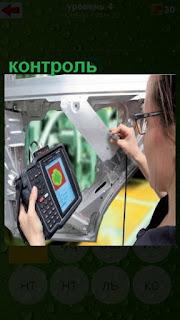 женщина с прибором проверяет качество сборки машины, контроль