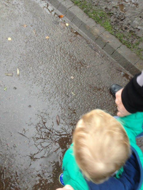toddler splashing in puddle wearing his wonderful wellies