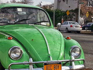 A green Volkswagen Bug parked on a side street in Staten Island with a license plate that reads Bic Boy