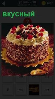На блюдце лежит приготовленный вкусный торт, который украшен красными ягодками сверху