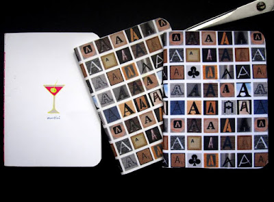 Three notebooks: one is white with a martini glass drawn on the cover. Two are covered with fabric printed with various letter As in wood tones.