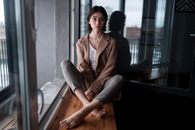 Chica sentada al lado de la ventana en la ciudad