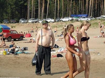 Lustige Strandbilder zum lachen Alter Mann und schöne Frauen im Bikini
