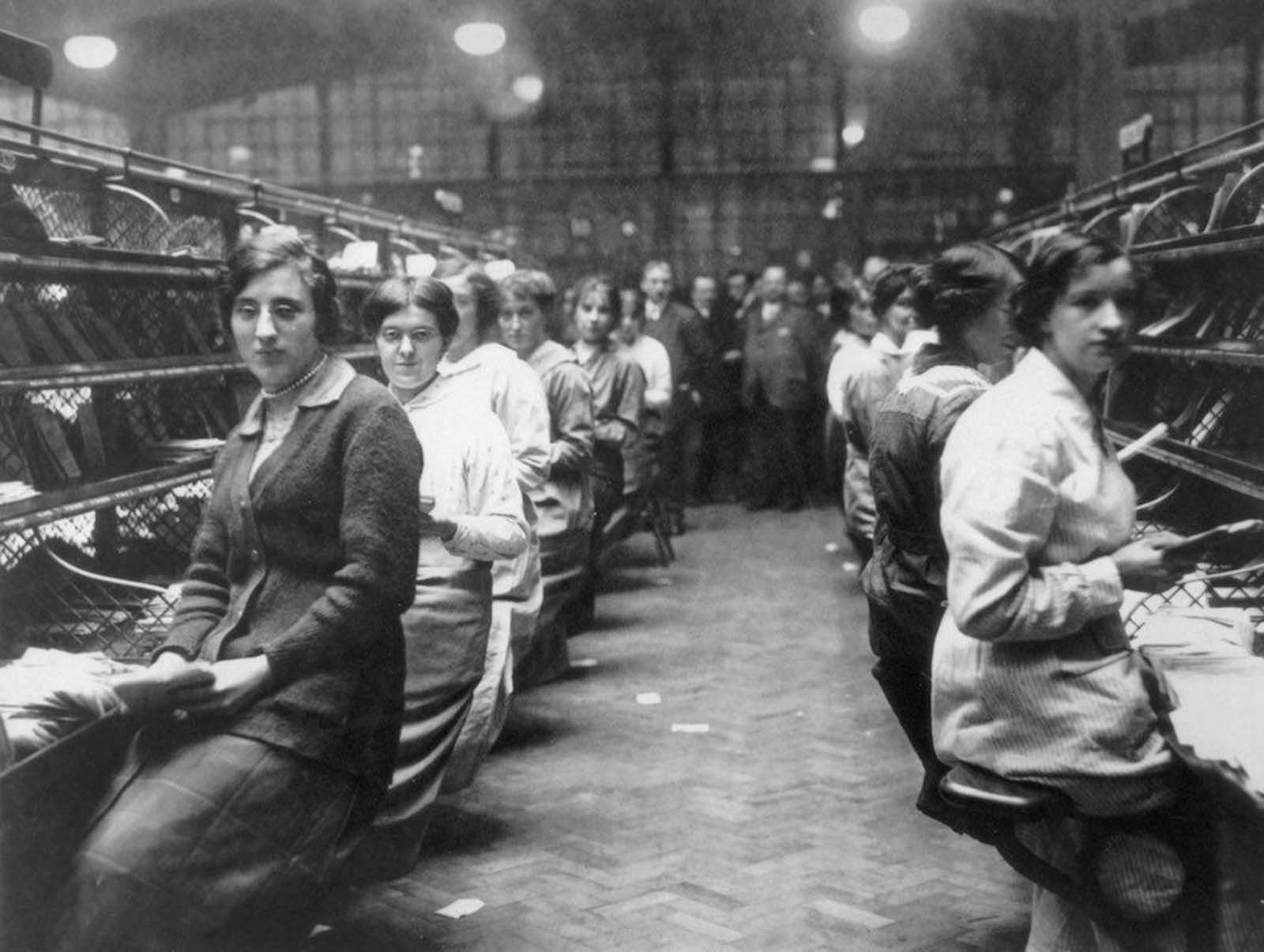 Women sorting mail at the post office during the Christmas rush in England. The women wear a range of blouses, and the woman front-left wears a cardigan and a set of pearls. Their hair is again worn loosely tied up. The woman front-right wears a striped dress, as we're starting to see more patterns. 1920.