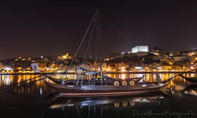 Vista nocturna de Oporto con barcos en el río Duero