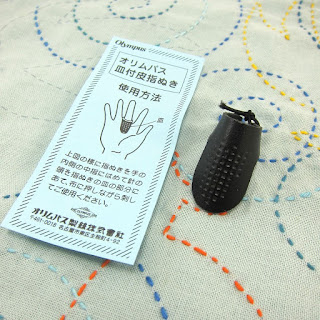black leather sashiko thimble (like a leather flap with holes drilled in a grid all over it) with packaging written on in Japanese